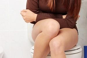 Девушка сидит на унитазе и собирает мочу для анализа